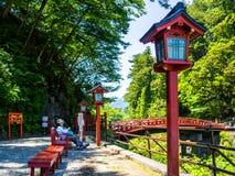 KYOTO JAPONIA, LIPIEC, - 05, 2017: Niezidentyfikowana kobieta używa jej telefon komórkowego przy outdoors w parku blisko drewnian Obraz Royalty Free