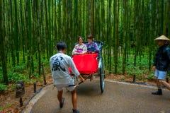 KYOTO JAPONIA, LIPIEC, - 05, 2017: Niezidentyfikowani ludzie nad czerwonym riksza w ścieżce przy pięknym bambusowym lasem przy Ar Zdjęcia Stock