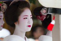 KYOTO, LIPIEC - 24: (festiwal) niezidentyfikowana Maiko dziewczyna lub Geiko dama na paradzie hanagasa w Gion Matsuri trzymający  zdjęcia royalty free