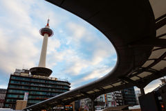 Kyoto tower against blue sky. KYOTO, JAPAN - NOVEMBER 23, 2016: Kyoto tower against blue sky with curve bus platform at Kyoto station Royalty Free Stock Photo