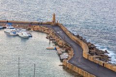KYRENIA, NORD-ZYPERN - 29. NOVEMBER 2015: die Leute, die durch den Pier in Mittelmeer gehen, fahren am Abend die Küste entlang Lizenzfreies Stockfoto