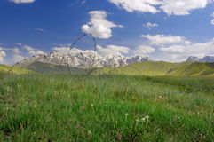 Kyrgyz pasture. Typical landscape of Kyrgyzstan - mountainous pasture, barbed wire fenced Stock Photography