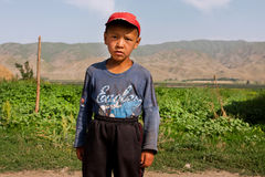 KYRGYZSTAN: Boy looks into the distance on the background of the mountains of Central Asia Stock Photos