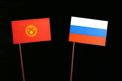 Kyrgyzstani flag with Russian flag isolated on black Royalty Free Stock Photos