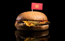 Kyrgyzstani flag on top of hamburger isolated on black Stock Image