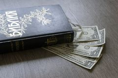 Kyrillische heilige Bibel mit Gelddollar Stockbilder