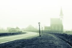 Kyrka av Den Hoorn i dimmig morgon för höst på den Texel ön i Nederländerna royaltyfri foto