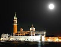 Kyrka av helgonet Geroge i Venedig vid natt och de ljusa slingorna Arkivfoto
