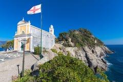 Kyrka av San Giorgio Portofino Stenig kustlinje och vågor Arkivfoton
