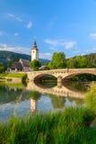 Kyrka av Sv John The Baptist och en bro vid Bohinj sjön Arkivfoto