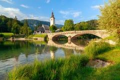 Kyrka av Sv John The Baptist och en bro vid Bohinj sjön Royaltyfria Foton