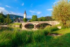 Kyrka av Sv John The Baptist och en bro vid Bohinj sjön Royaltyfria Bilder