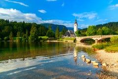 Kyrka av Sv John The Baptist och en bro vid Bohinj sjön Royaltyfri Bild
