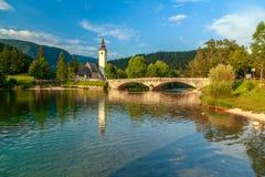 Kyrka av Sv John The Baptist och en bro vid Bohinj sjön Royaltyfri Foto