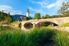 Kyrka av Sv John The Baptist och en bro vid Bohinj sjön Royaltyfri Fotografi