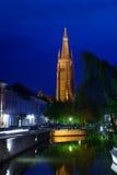 Kyrka av vår dam Bruges på natten från kanalen Arkivfoto