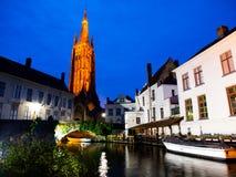 Kyrka av vår dam i Bruges på natten arkivbilder