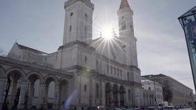 Kyrka för St Ludwin i Munich mot solljuset med en stor solljuslensflare i - mellan churchtowersna långsam rörelse arkivfilmer