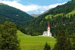 Kyrka i den alpina dalen arkivfoto