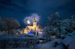 Kyrka i det snöig vinterlandskapet med fyrverkerier, fira royaltyfria foton