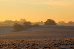 Kyrka i dimmig soluppgång i Februari Arkivfoto