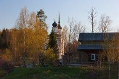 Kyrka, landshus och vårbjörkträd arkivfoto