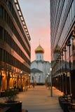 Kyrka mellan exponeringsglaskontorsbyggnader på solnedgången fotografering för bildbyråer