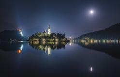 Kyrka och blödd slott på den blödde sjön i Slovenien på natten Arkivfoton