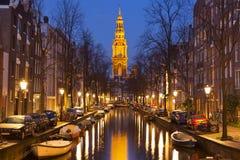 Kyrka och en kanal i Amsterdam på natten Arkivbilder