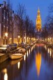 Kyrka och en kanal i Amsterdam på natten arkivfoto