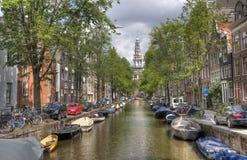 Kyrka och kanal i Amsterdam fotografering för bildbyråer