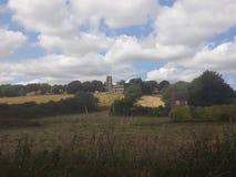Kyrka och by på en kulle royaltyfria foton