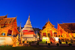 Kyrka och pagod på den Phra Singh templet med skymning Royaltyfri Fotografi