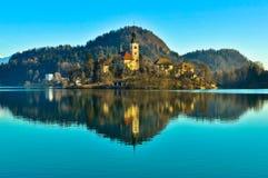 Kyrka på ön i sjön med berglandskap Arkivbilder