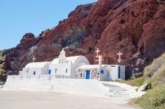 Kyrka på den Santorini ön på den röda stranden Arkivfoto