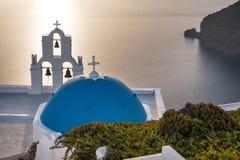Kyrka på Santorini på den guld- solnedgången Arkivbild