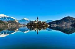Kyrka på ön i sjön med berglandskap Arkivfoto
