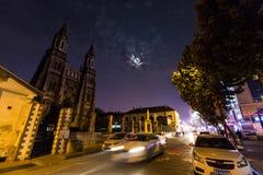 Kyrka under månen i en livlig gata royaltyfri foto