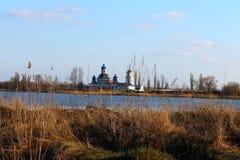 Kyrkan är långväga Landskap Det delas av floden Och torrt gräs Ett naturligt landskap Arkivbild