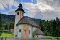 Kyrkan av den heliga anden på sjön Bohinj, Slovenien Arkivfoto