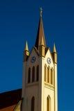 Kyrkan står hög med blåttskyen Royaltyfri Bild