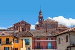 Kyrkas klockatorn och färgrika hus i La Morra Arkivbild