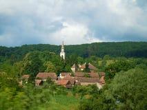 Kyrkatorn som stiger från de gröna träden royaltyfria bilder