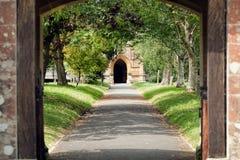 Kyrklig bana Fridsamt träd fodrad bana till och med kyrkogård Arkivfoto