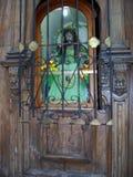 Kyrklig dörr med den forntida Kristusstatyn Arkivbild