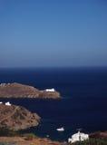 Kyrklig kloster på udden i det Aegean havet med hus och boaen royaltyfria bilder