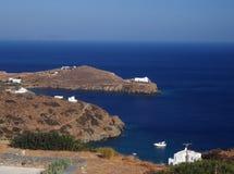 Kyrklig kloster på udden i det Aegean havet med hus och boaen arkivbild