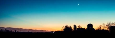 Kyrklig kontur på solnedgången med den växande månen Arkivbilder