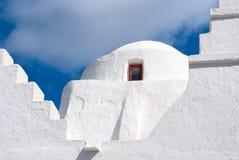 Kyrklig kupol med det lilla fönstret i Mykonos, Grekland Detalj för kapellbyggnadsarkitektur Vitkyrka på molnig blå himmel Arkivfoto