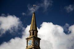 Kyrklig kyrktorn och klocka mot en blå molnig himmel Arkivfoto